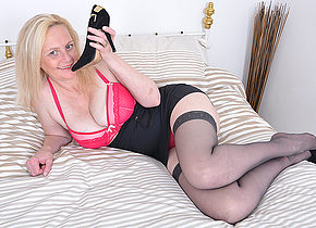 Naughty blonde mature lady playing with her pussy in bed