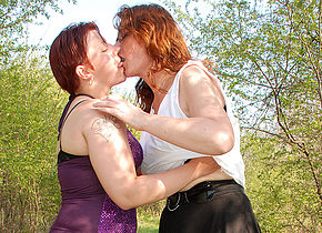 two old and young lesbians go at outside in the woods